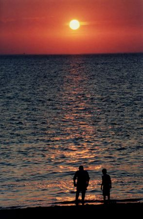 influx: Silhouette of two boys standing in ocean at shoreline at sunset.