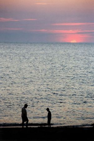 influx: Silhouette of two children on oceans edge at sunset.