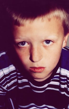 resent: Closeup portrait of unhappy boy; cross-processed for unusual coloring. Stock Photo