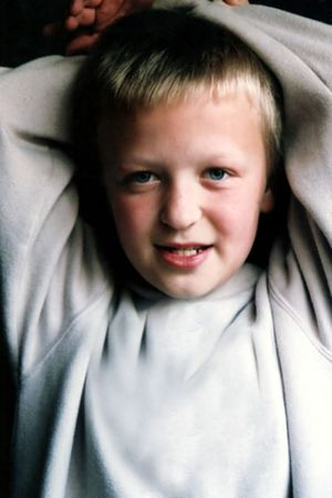 Boy with arms above his head, lit by natural light from window.