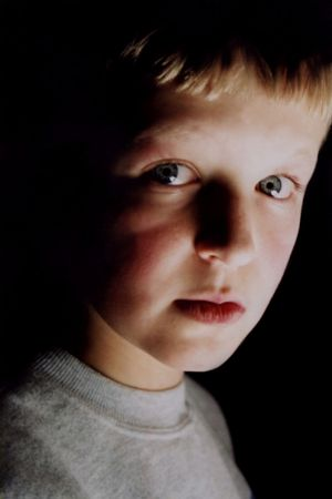Vertical portrait of boy with ghostly lighting.