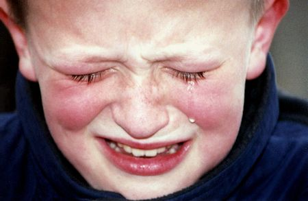 dismal: Closeup of boy crying. Stock Photo