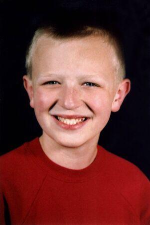 Portrait of preteen boy in red shirt.