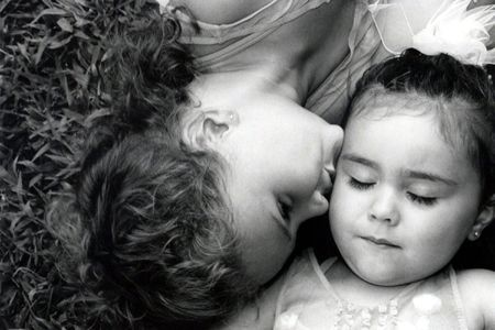 Black and white of two sisters, the older kissing the younger.