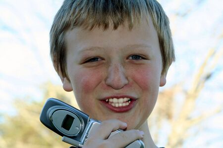Preteen boy talking on a cell phone.
