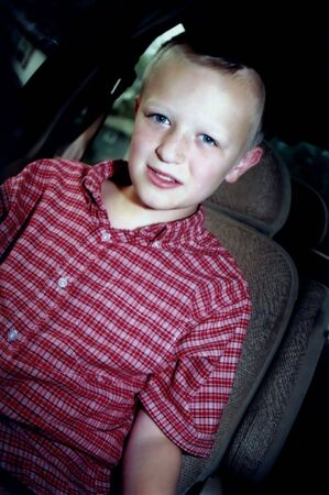 Portrait of preteen boy in a car; photograph angled.
