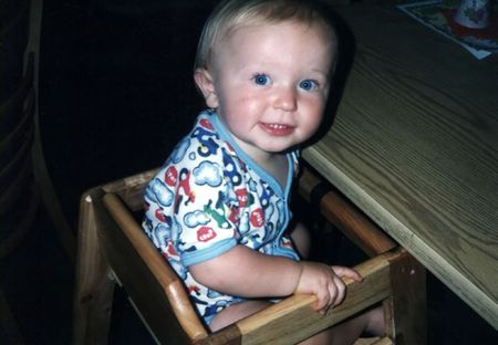 Toddler sitting in a highchair at a table, looking back.