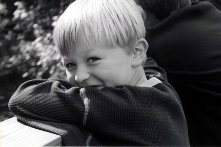 Black and white portrait of young boy with devilish expression.