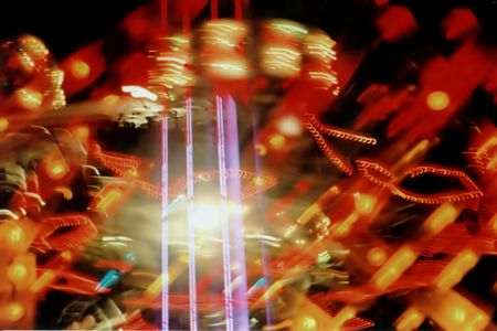 queasy: Abstract of moving amusement ride at night.