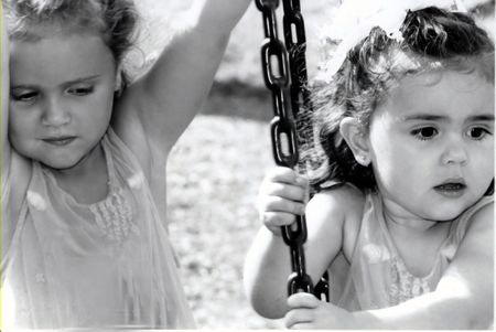 Black and white of two sisters on a tire swing, not smiling. Фото со стока