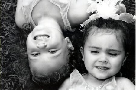 Black and white of two sisters laying in grass with heads in opposite directions. Reklamní fotografie