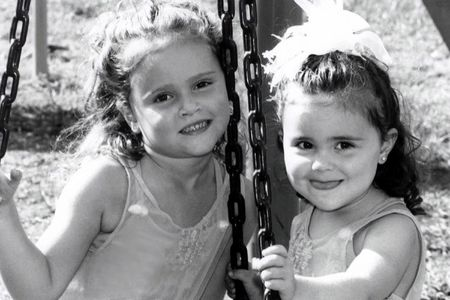 Black and white portrait of two sisters on a tire swing.