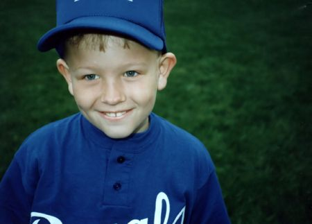 Young boy in little league baseball uniform. Imagens