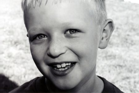 Black and white portrait of a smiling boy.