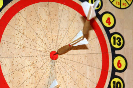 Dartboard with two darts back to back in bullseye.