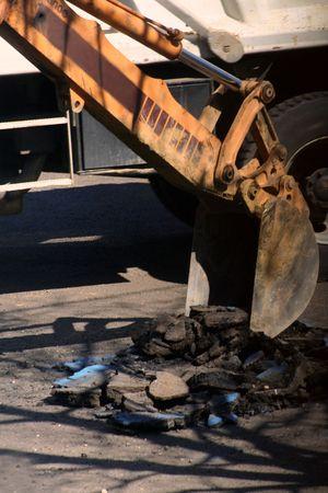 Backhoe digging into asphalt street.