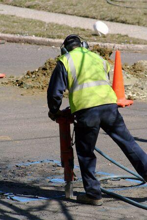 gouge: Worker using a jackhammer.