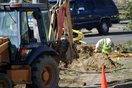 Utility workers with a backhoe. Imagens