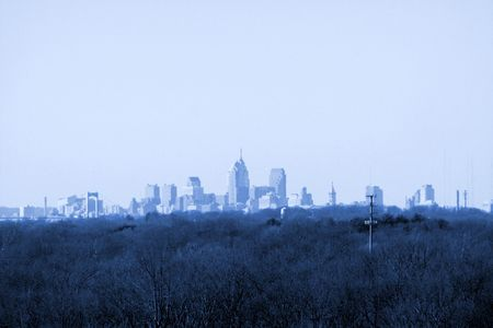 contradict: Skyline of Philadelphia, PA, from suburban southern New Jersey.  Overall photograph tinted blue. Stock Photo