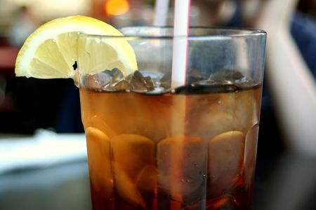 Top half side view of a glass of iced tea with a straw and lemon on the side. Stock Photo