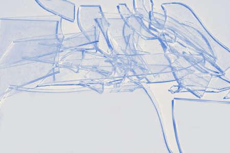 Broken glass tinted blue. Фото со стока