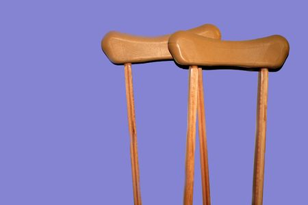 Set of crutches on lavendar background. Banco de Imagens