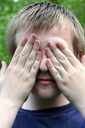 blinder: Preteen boy covering eyes with both hands.