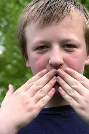 squelch: Preteen boy covering his mouth with both hands.