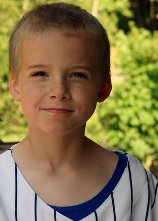 ornery: Portrait of boy in baseball jersey with intent expression.