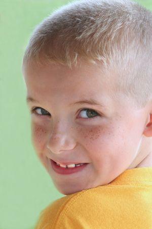 Portrait of smiling boy looking over shoulder.