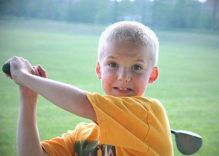 aggressively: Boy swinging a golf club aggressively.