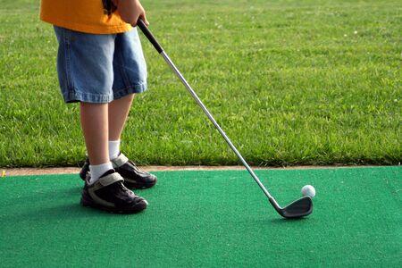 Boy hitting a golf ball at a driving range.