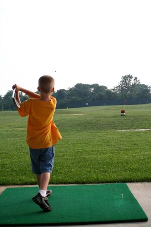 Boy hitting a golf ball at a driving range.