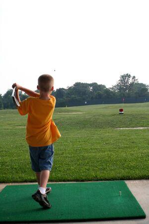 Chico golpear una pelota de golf en un driving range.  Foto de archivo - 538594