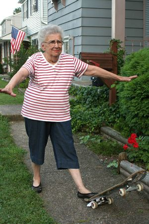 Senior citizen woman with tilted skateboard. Stock Photo