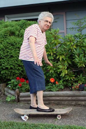 Senior citizen woman on a skateboard.