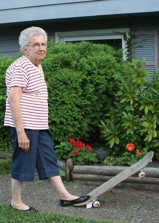 Senior citizen standing on tilted skateboard. Imagens