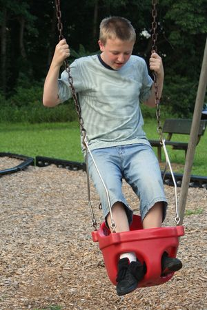 Teenage boy standing on a  swing.