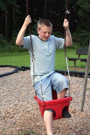 uncoordinated: Teenage boy trying to get into  swing.