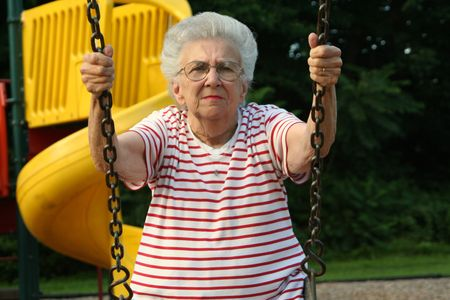 peppy: Senior citizen woman on a playground swing.