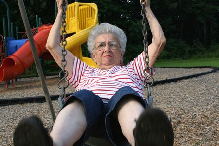 ornery: Senior citizen woman swinging on playground swing with grouchy expression.