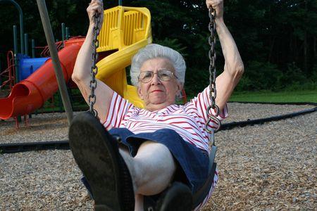 peppy: Senior citizen woman swinging on a playground swing.