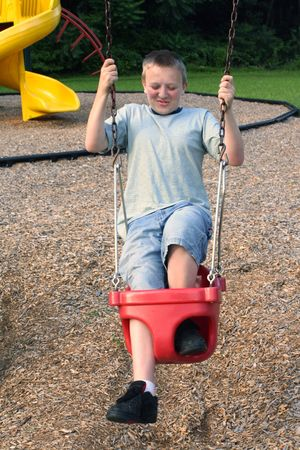 uncoordinated: Teenage boy trying to fit into a  swing. Stock Photo