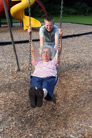 unnatural: Teenage grandson pushing grandmother on a playground swing.