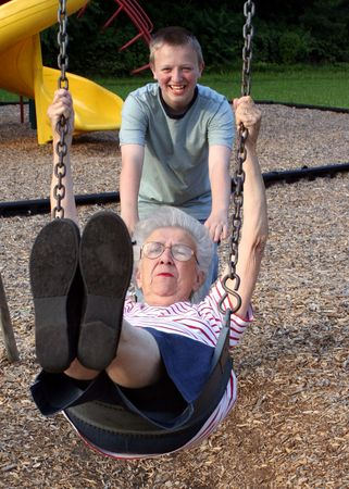 Teenage grandson pushing grandmother on a playground swing.