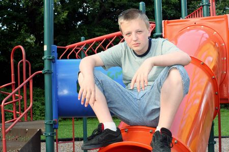 relive: Pensive teenage boy sitting on top of playground equipment.