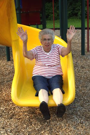 Senior citizen woman with arms upraised on a playground sliding board.