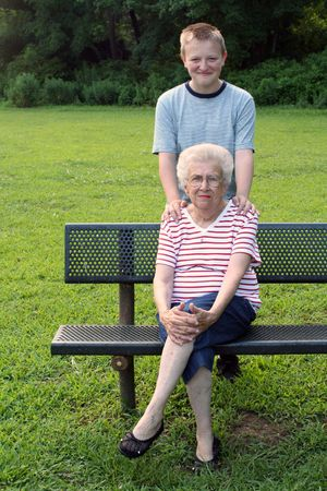 Grandson standing behind grandmother, seated on a park bench.