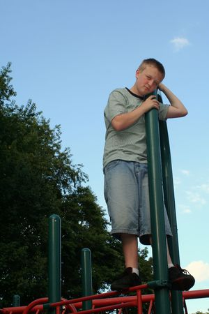 wistful: Wistful teenage boy standing on playground equipment.