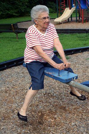 Senior citizen woman on a seesaw.